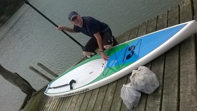 Peter with his paddle board and some of the rubbish he collected in Latham Bay